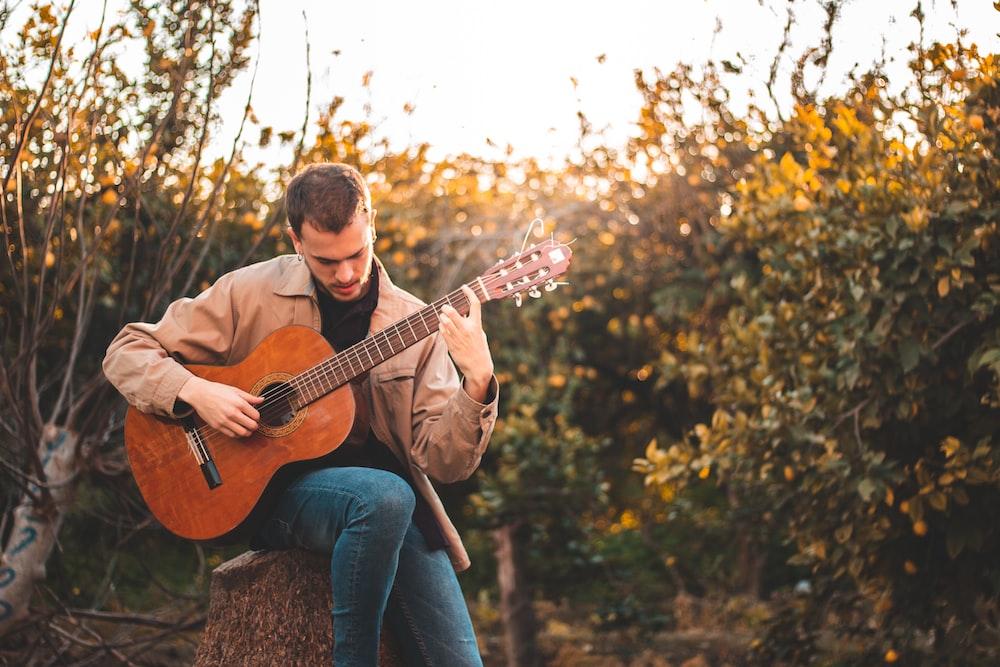 man in brown dress shirt playing acoustic guitar
