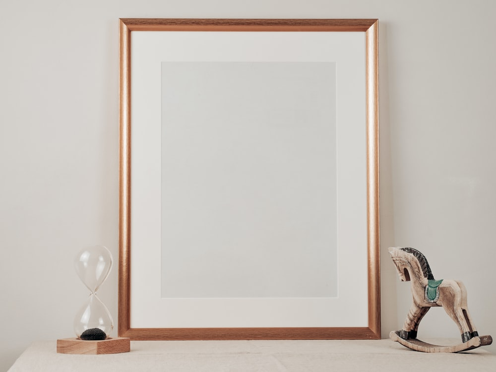 white wooden framed mirror on brown wooden table