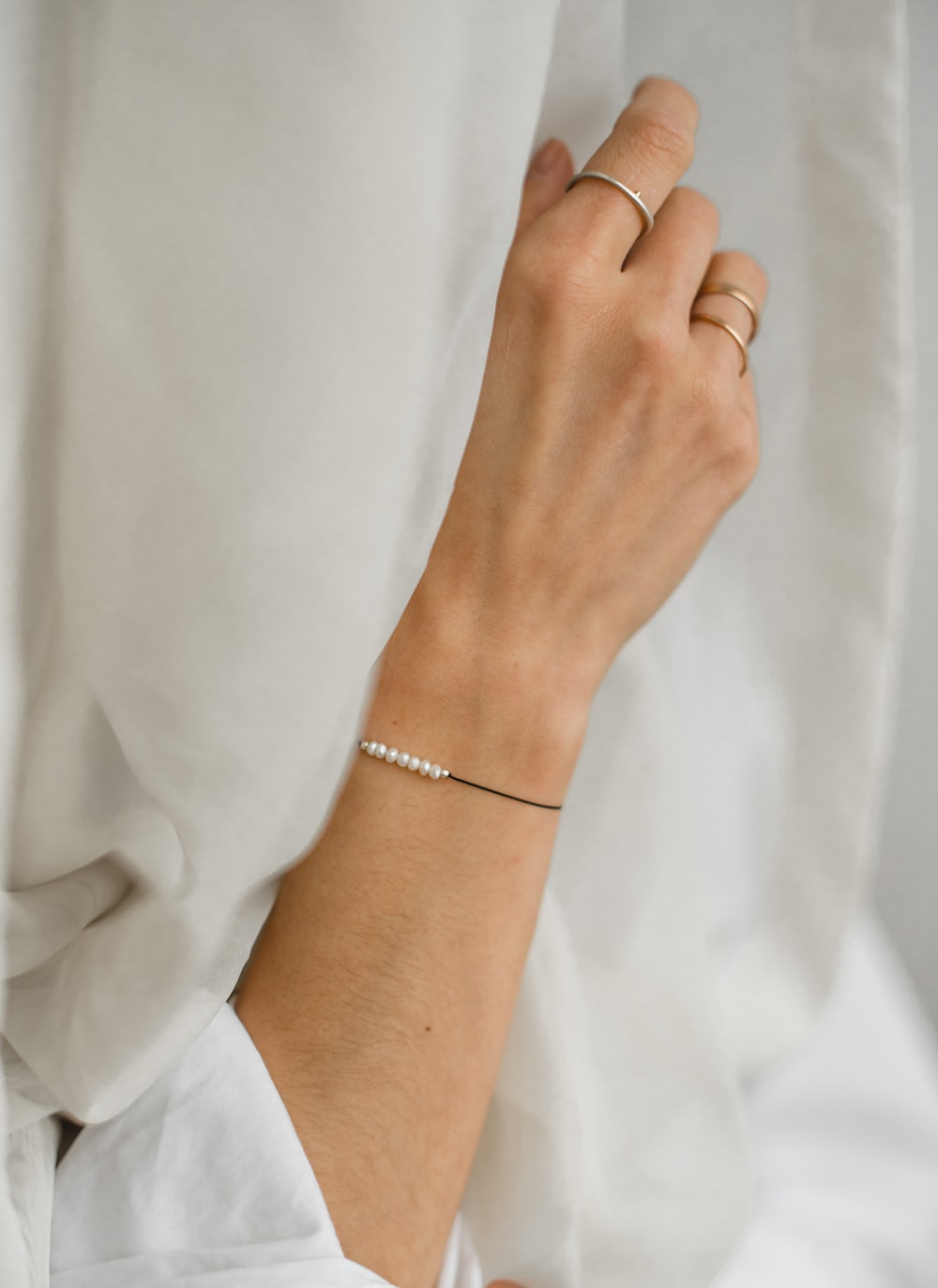 person wearing silver bracelet and white dress shirt