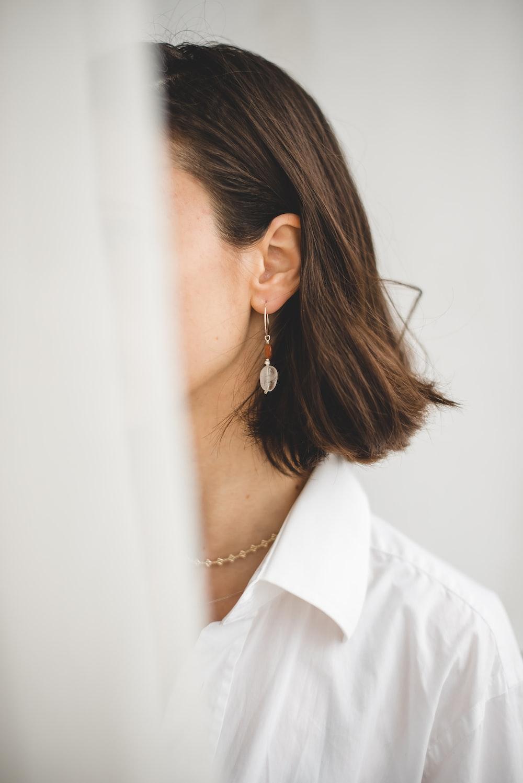 woman in white shirt wearing silver earrings