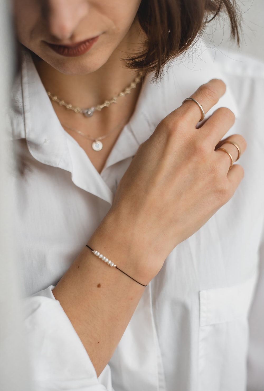 woman in white button up shirt wearing gold bracelet