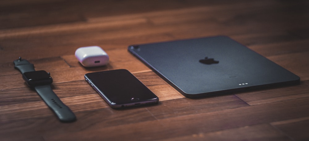 black ipad beside white apple magic mouse on brown wooden table