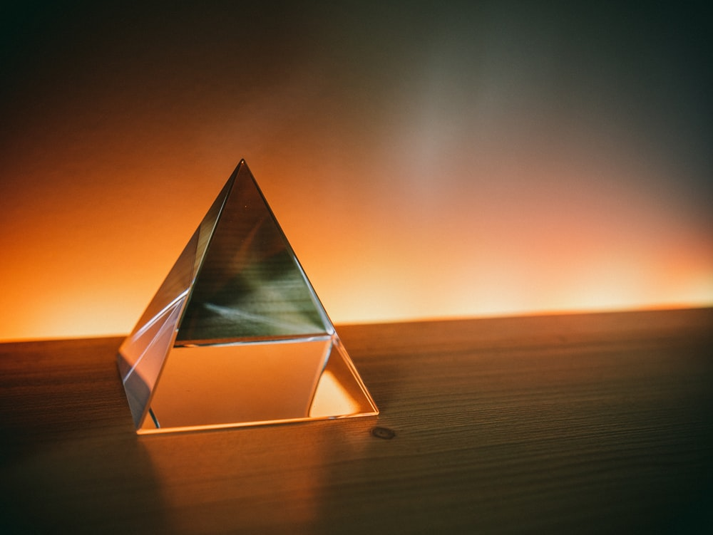 triangular brown and white wooden frame on brown sand during sunset