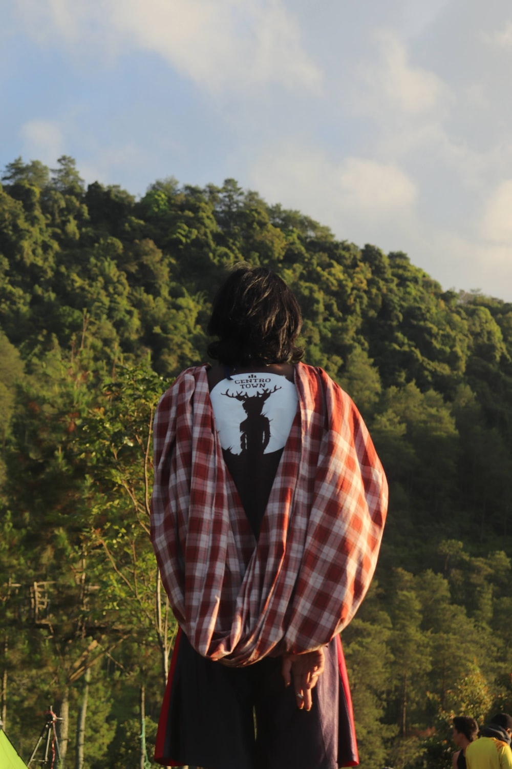 woman in red white and black plaid jacket standing on mountain during daytime