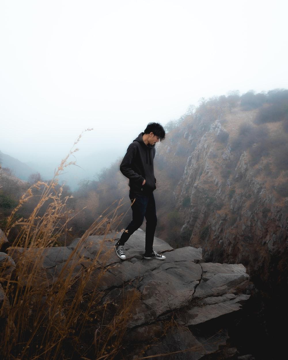 man in black jacket standing on rock during daytime