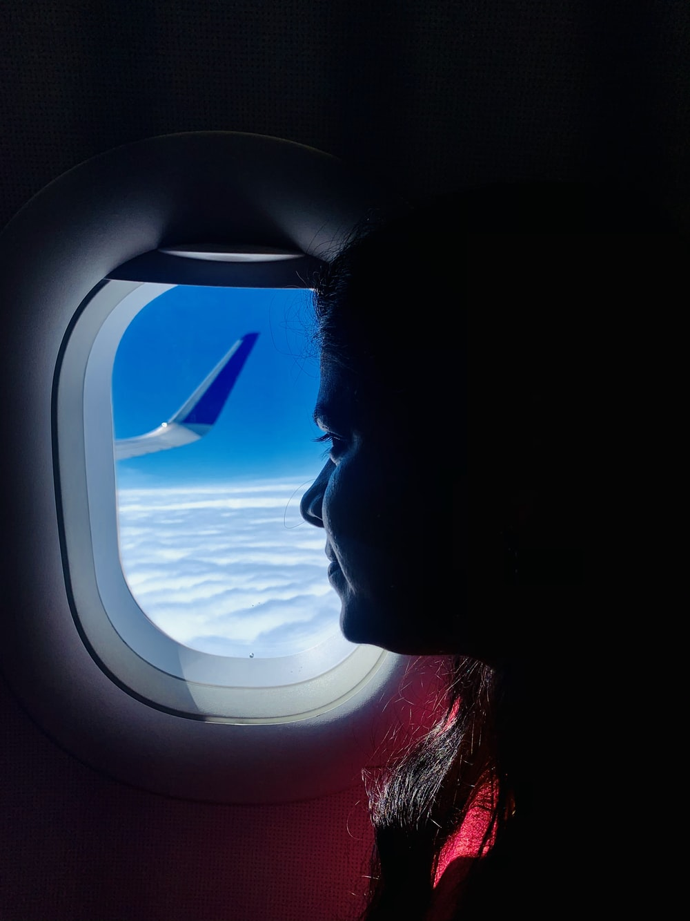 woman looking at the window of airplane