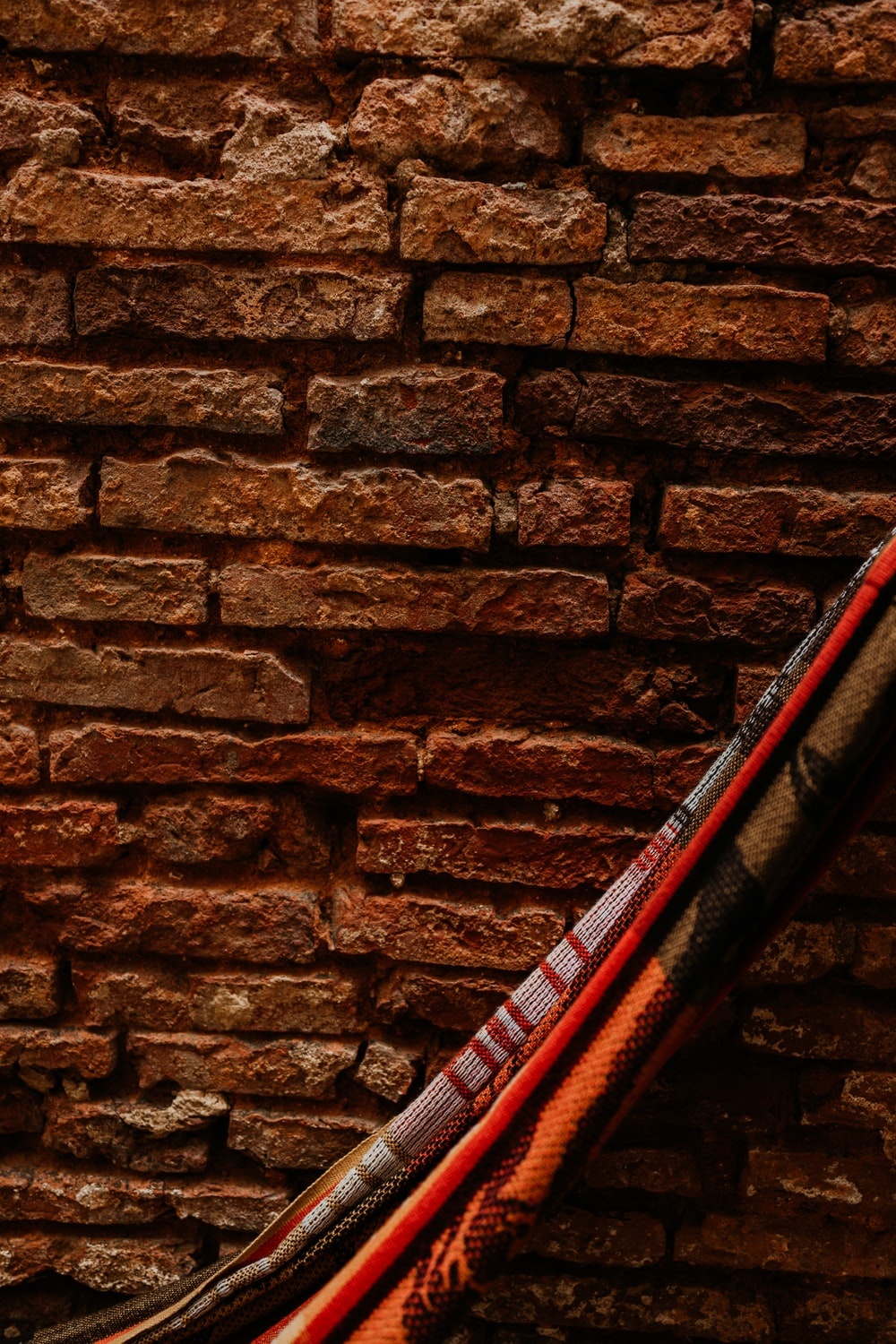 red and black electric guitar leaning on brown brick wall