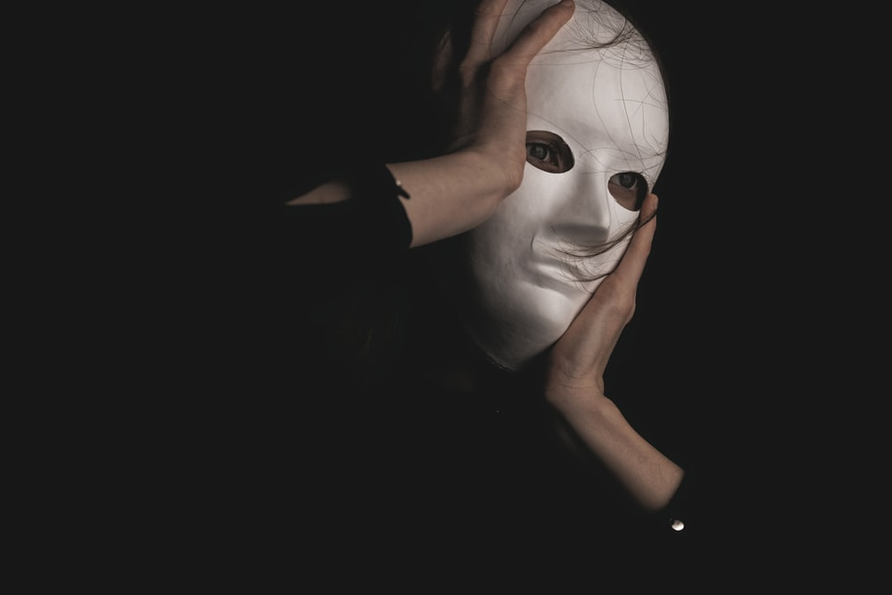 person in black long sleeve shirt covering face with face