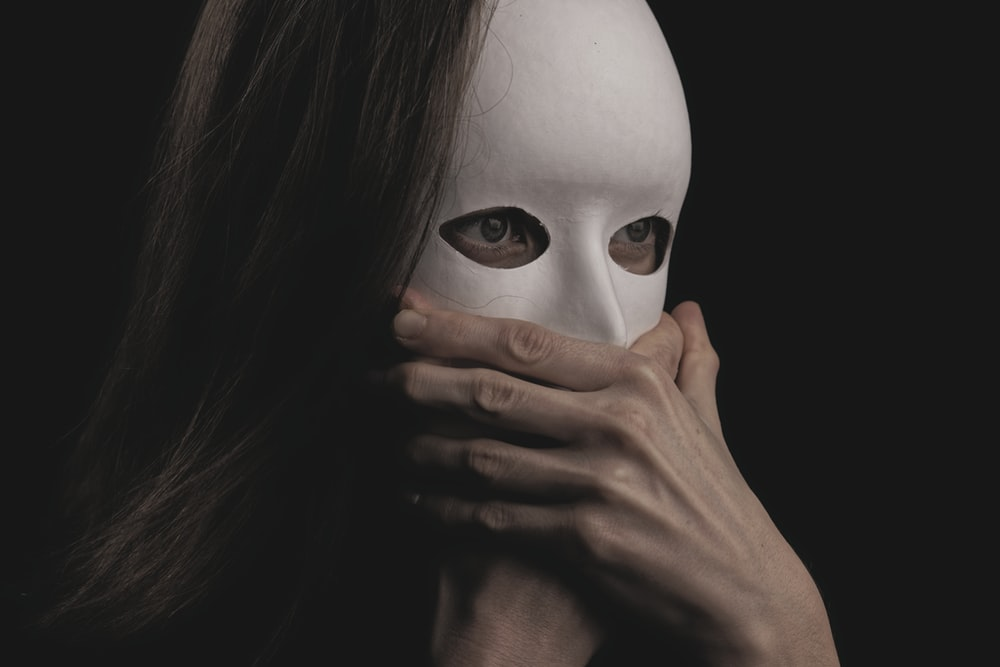 woman covering face with white mask