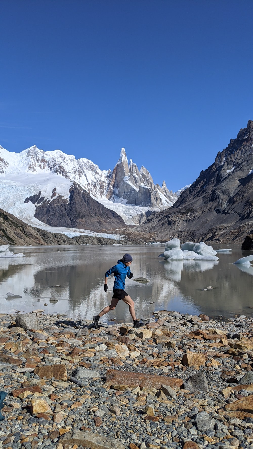 man in blue shirt and black shorts standing on rocky shore near snow covered mountain during