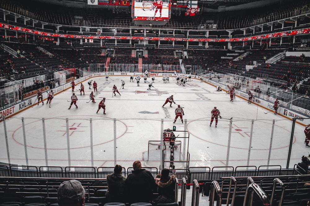 people playing ice hockey on stadium during daytime