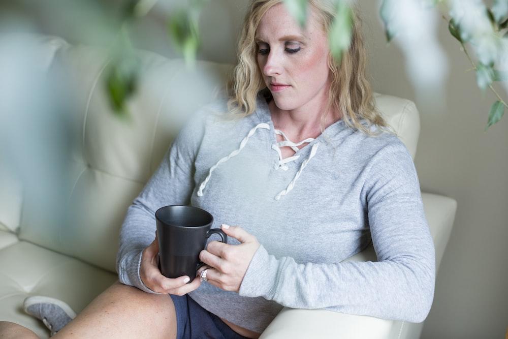 woman in gray long sleeve shirt holding black ceramic mug