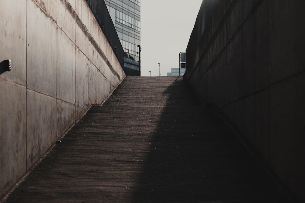 brown wooden pathway between concrete walls