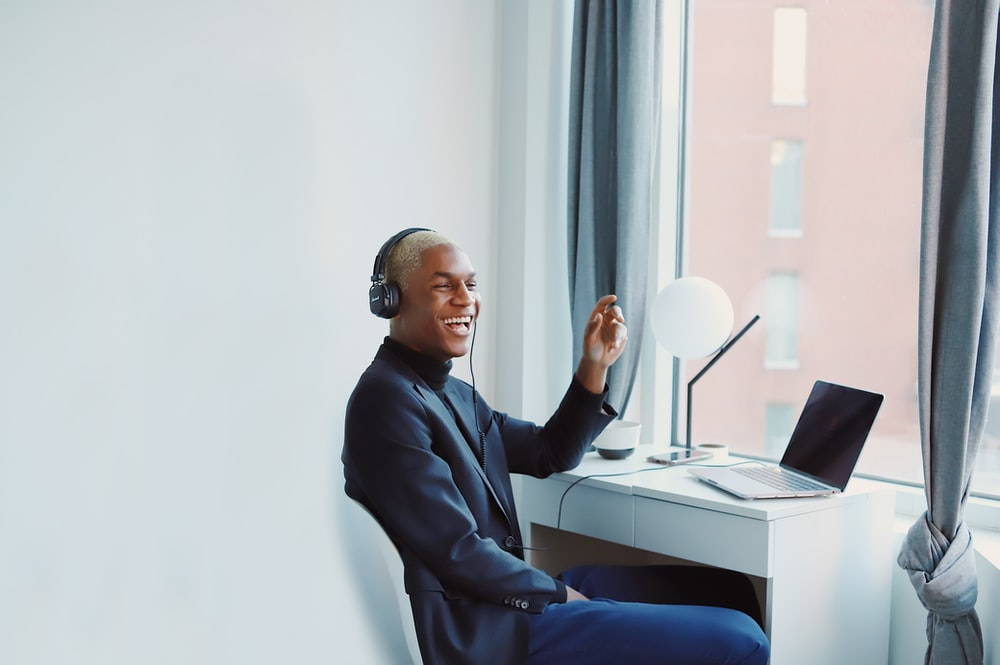 man in black long sleeve shirt sitting on blue chair