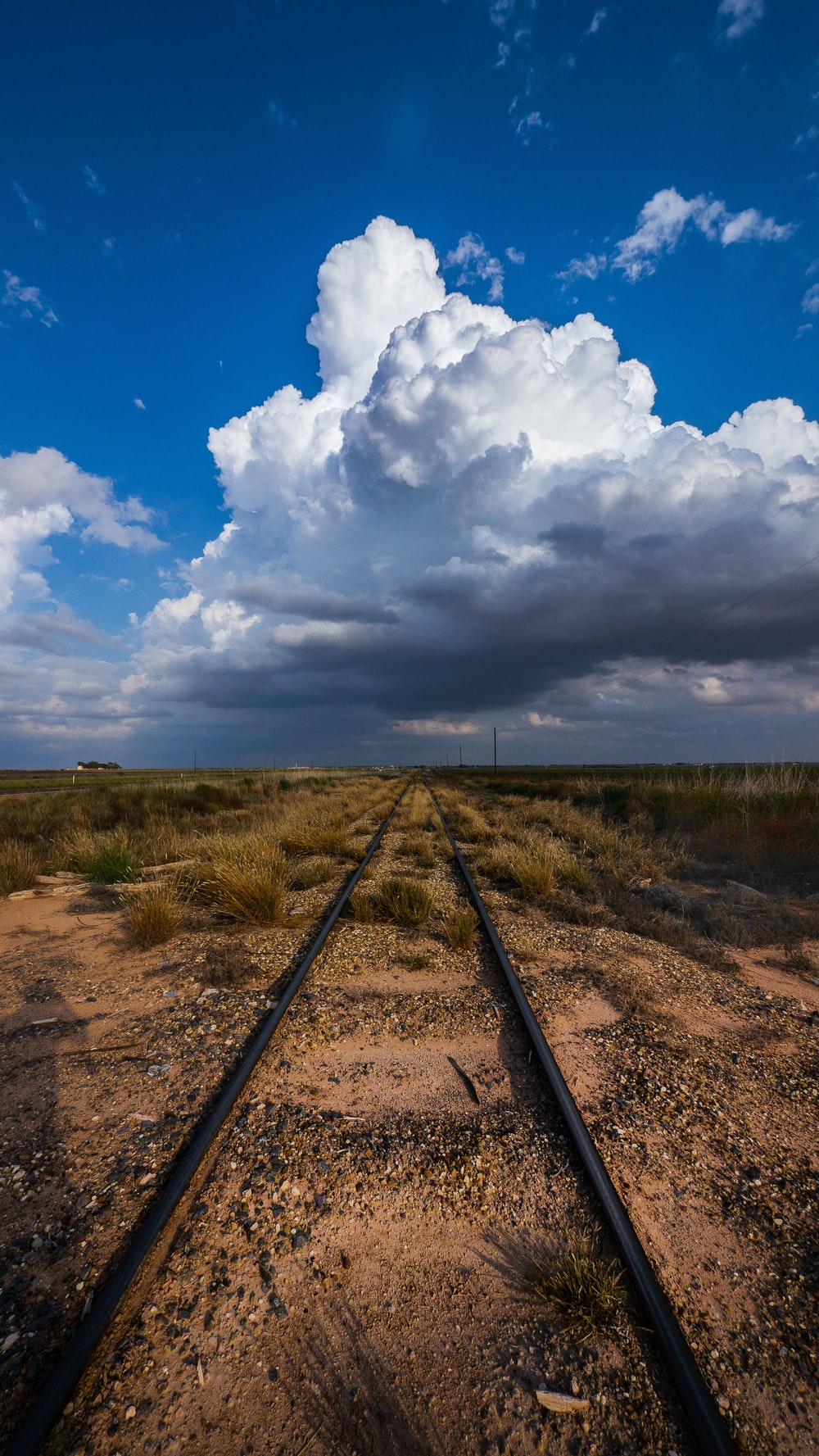train rail under blue sky and white clouds during daytime
