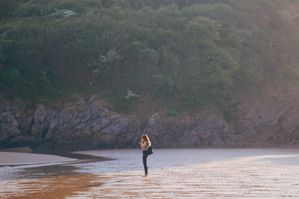 woman in black dress walking on brown sand near body of water during daytime