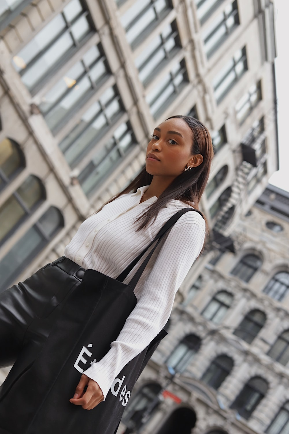 woman in white long sleeve shirt and black leather sling bag