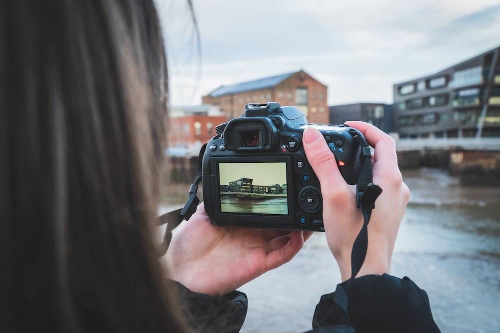 person holding black dslr camera during daytime