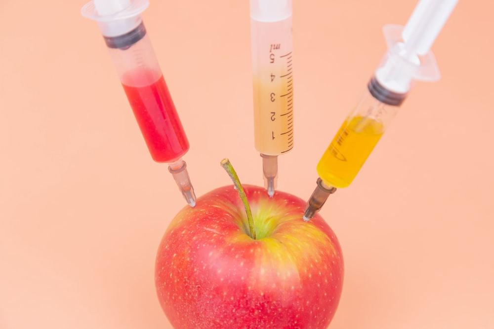 red apple beside clear glass bottle