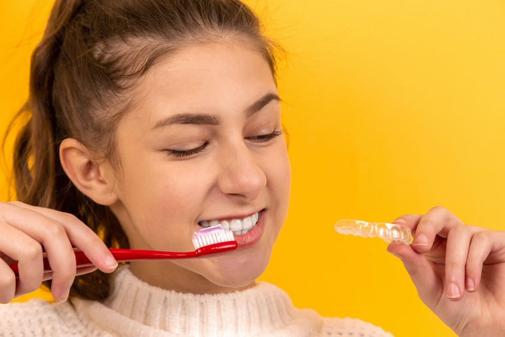 smiling girl in white sweater holding red and white toothbrush