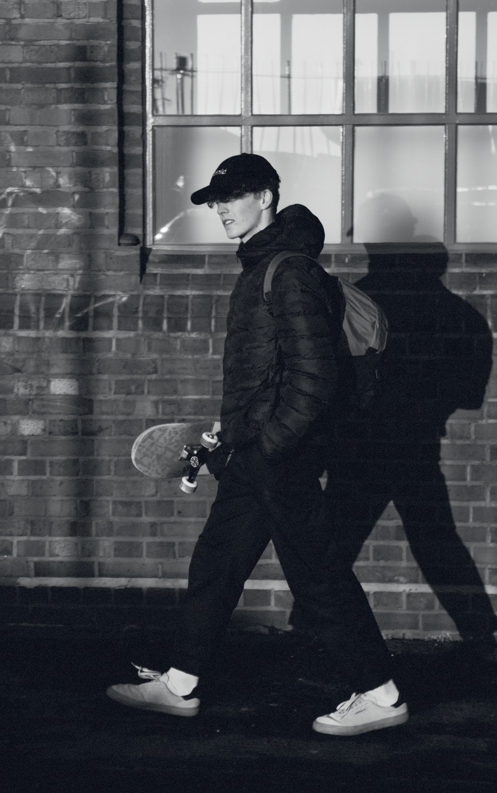 man in black jacket and black pants standing beside brick wall