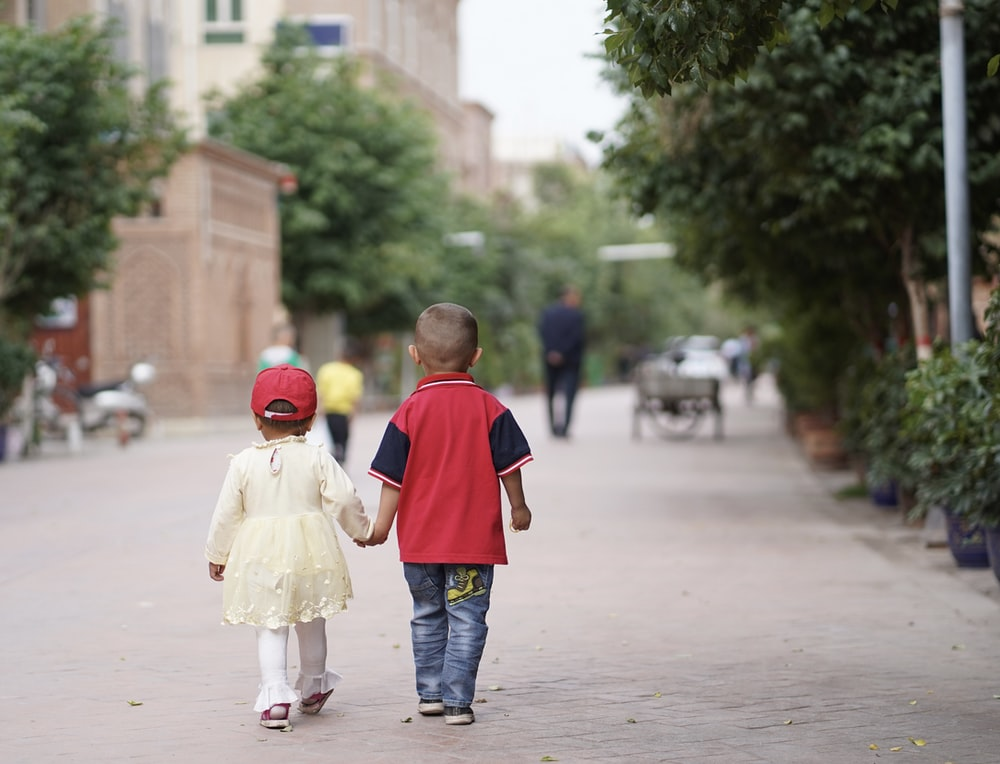 boy in red and blue shirt and gray pants holding girl in white dress during daytime
