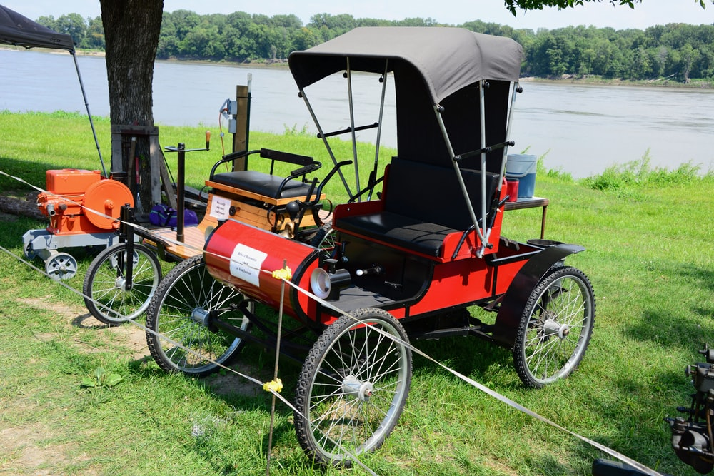 red and black vintage car on green grass field near body of water during daytime