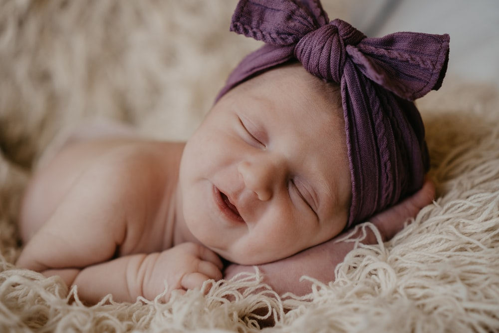 baby in purple knit cap lying on white fur textile