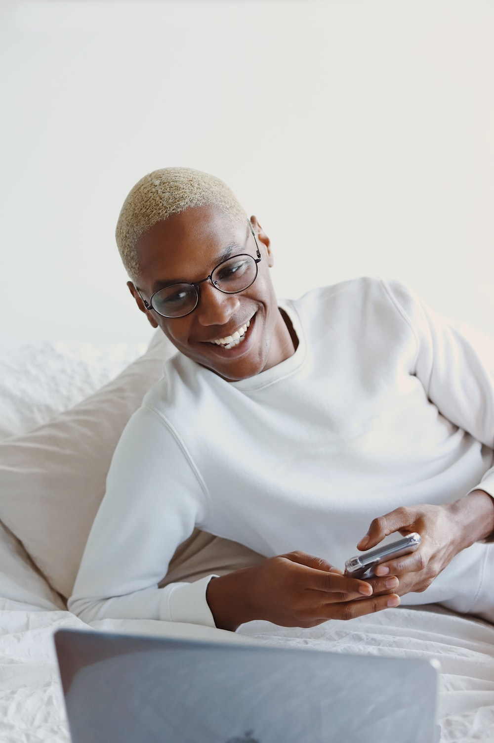 woman in white turtleneck sweater holding smartphone