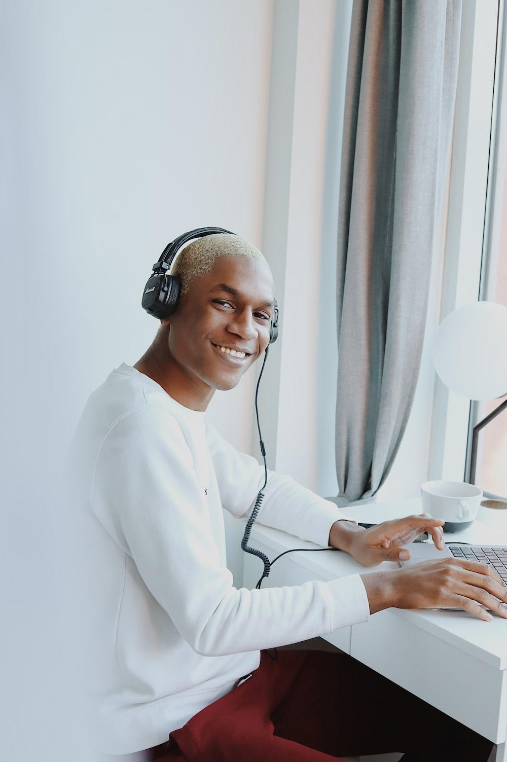 woman in white long sleeve shirt wearing headphones