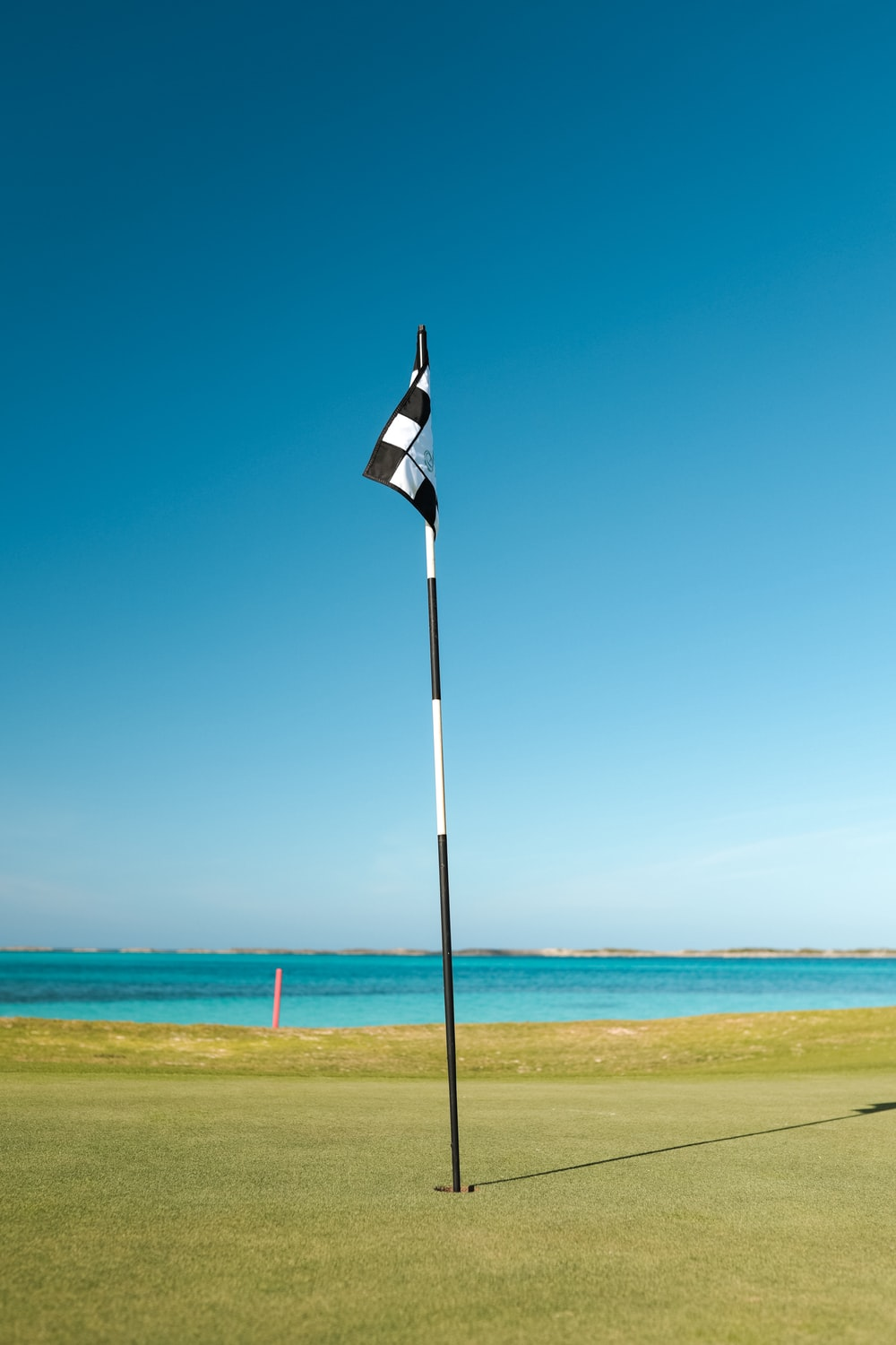 flag of us a on pole by the sea under blue sky during daytime