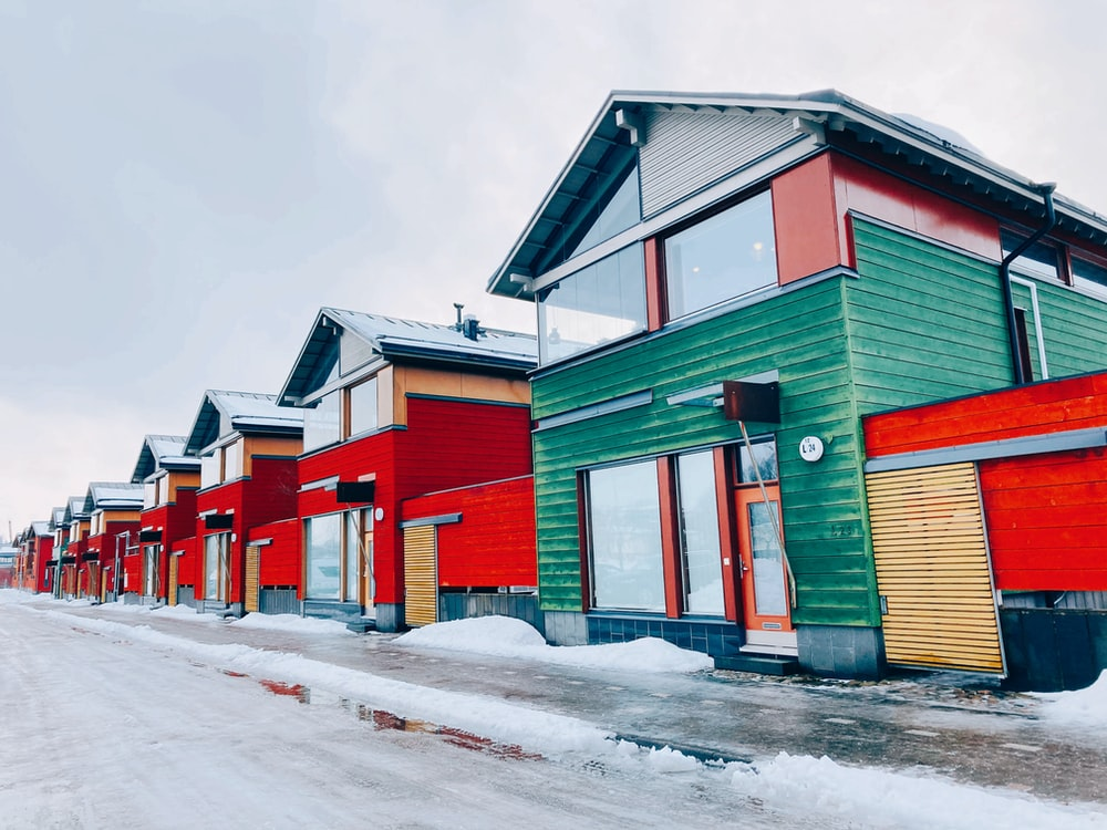 red green and yellow houses on snow covered ground