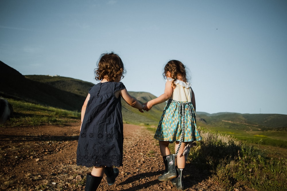 2 girls in blue dress standing on brown field during daytime