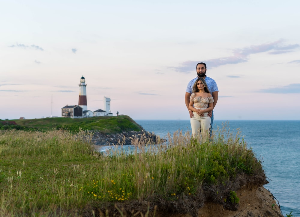 man in brown and white plaid dress shirt standing on green grass field near white lighthouse