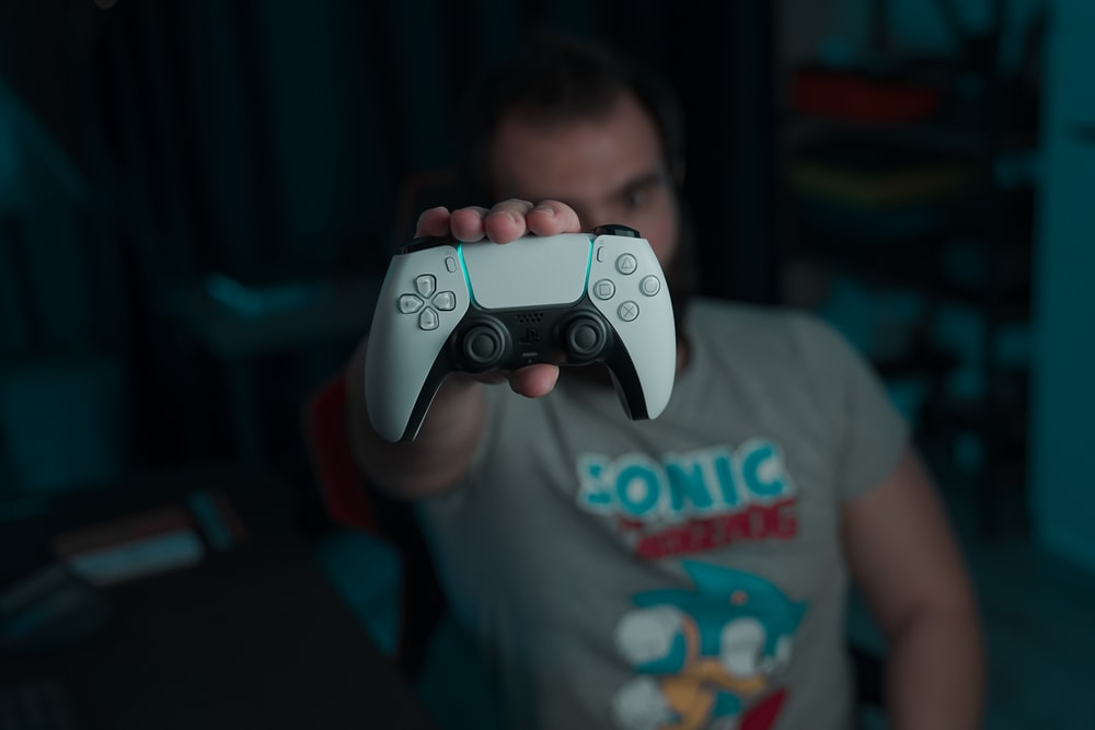 boy in gray and red crew neck t-shirt holding gray game controller