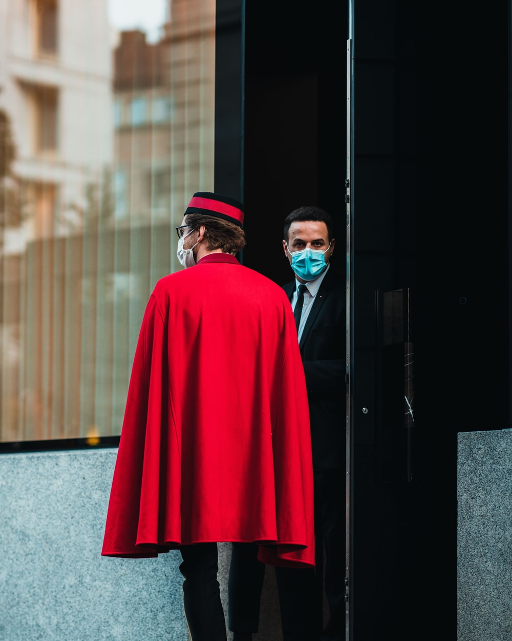man in red coat standing near brown building during daytime