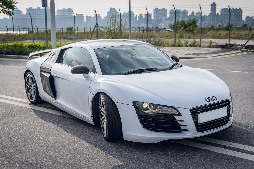 white audi r 8 parked on parking lot during daytime