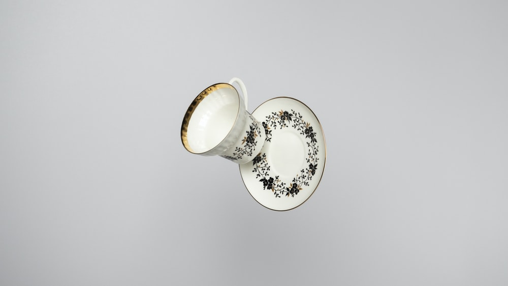 white and gold floral ceramic teacup