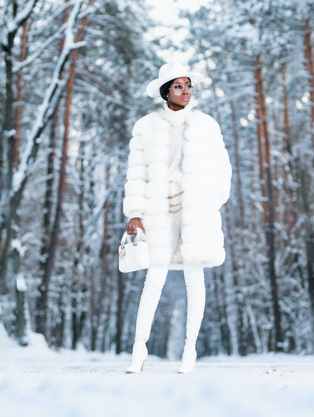 woman in white coat standing on snow covered ground