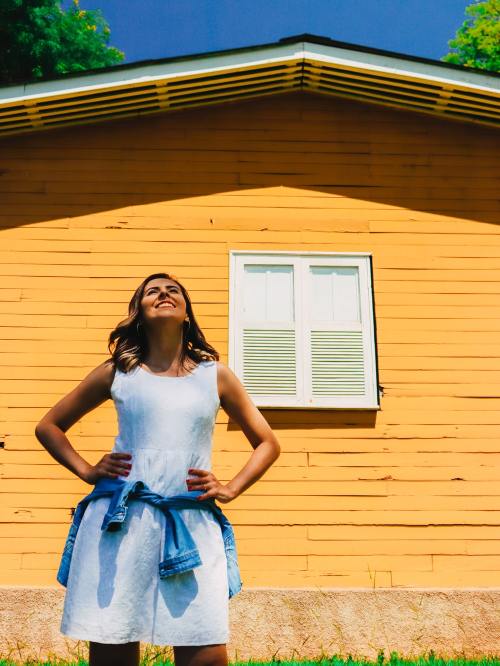 woman in white tank top and blue skirt standing in front of yellow house