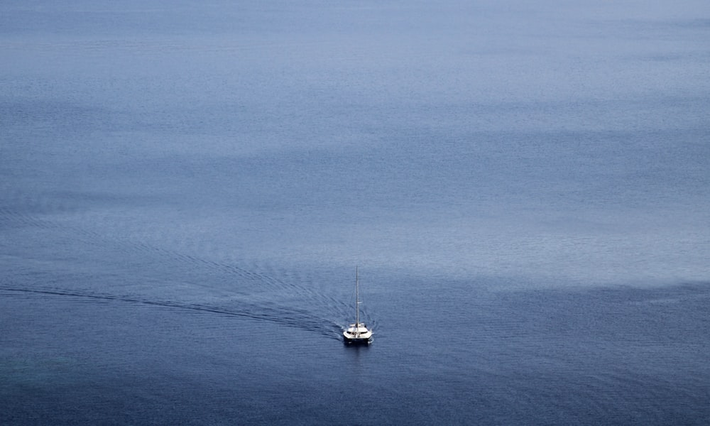 white boat on blue sea under blue sky during daytime