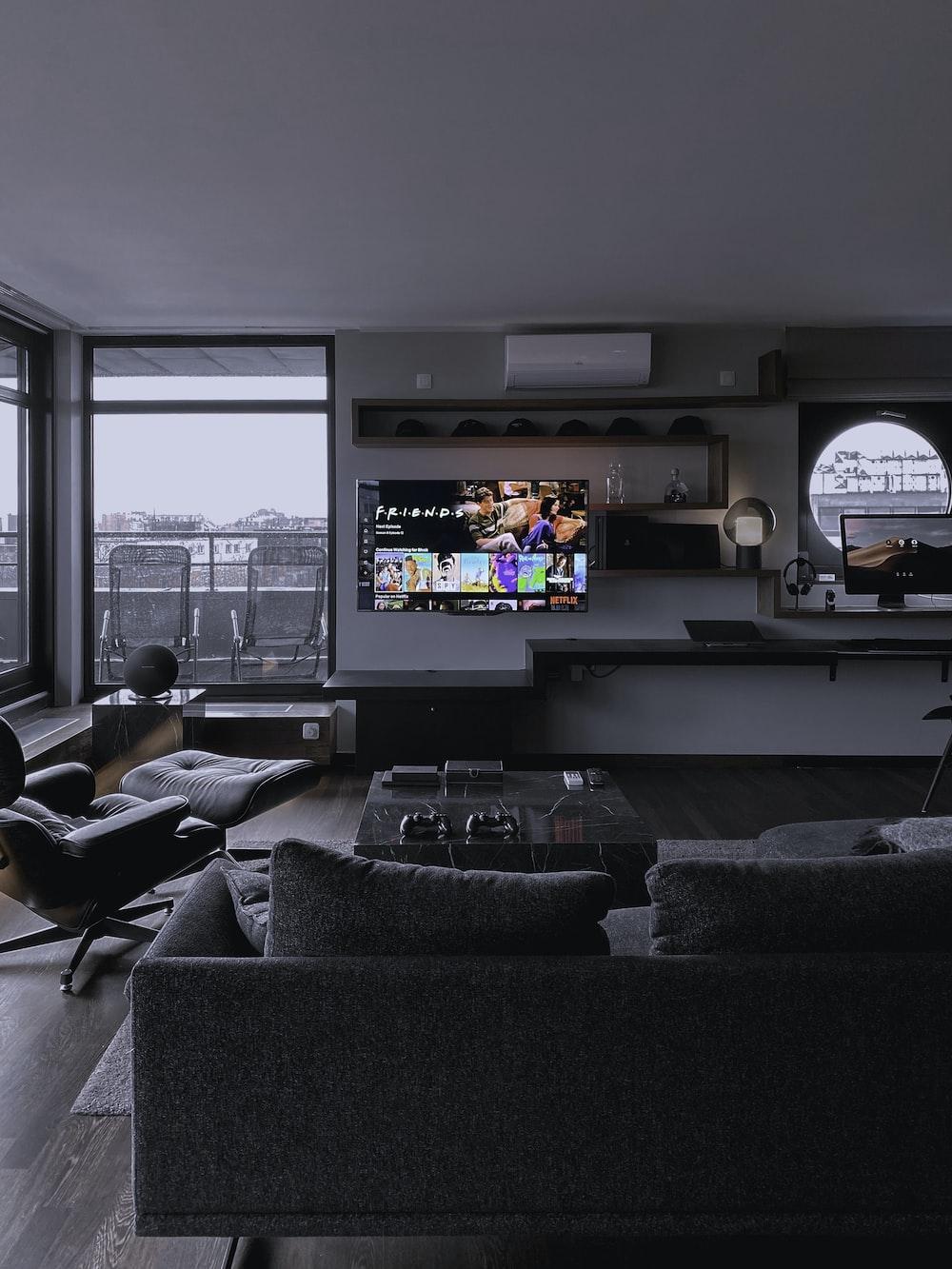 black flat screen tv turned on near window