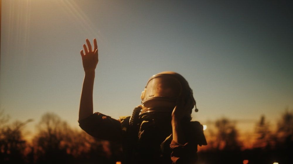 silhouette of man raising his right hand