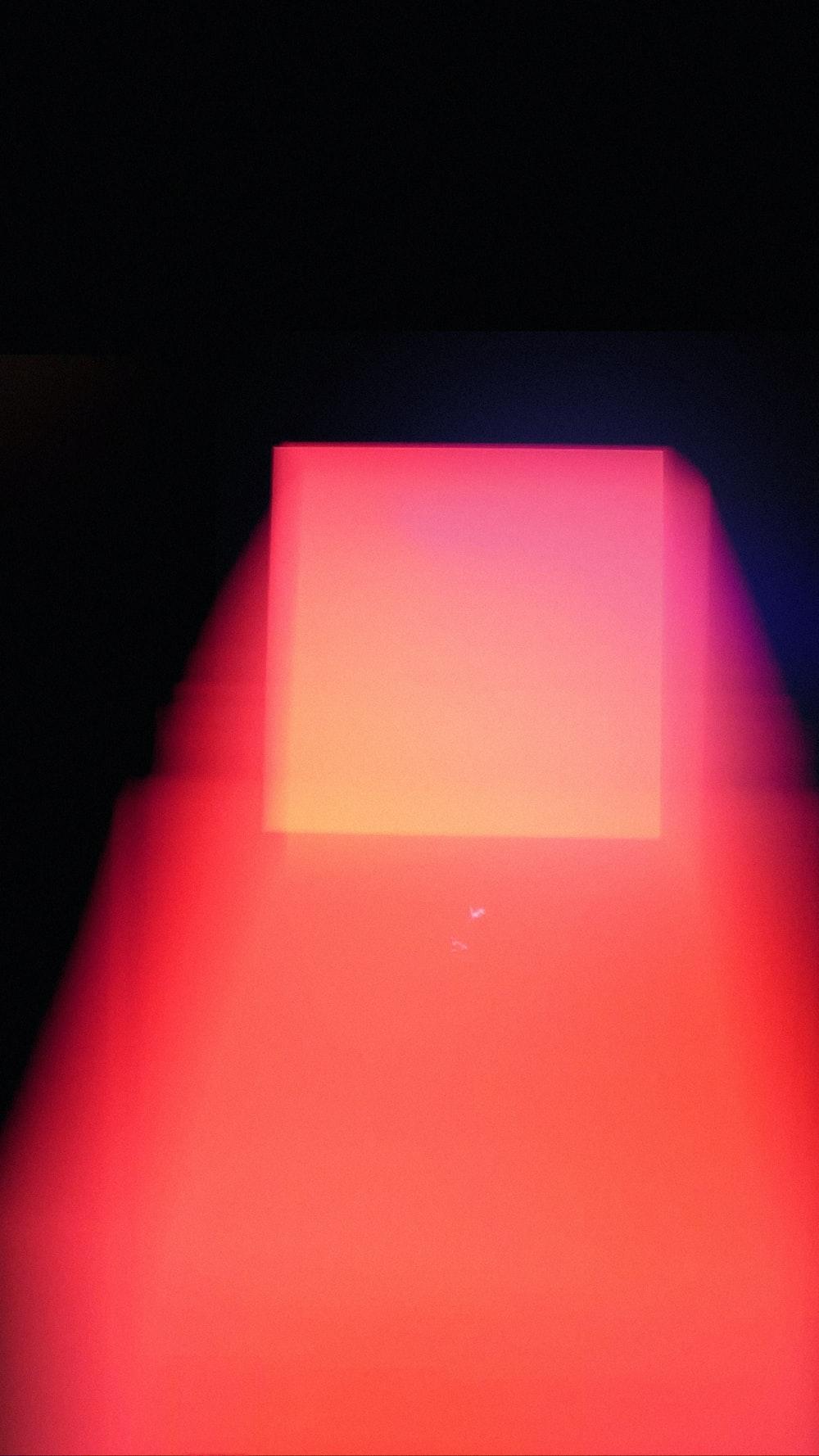 pink rectangular paper on black surface