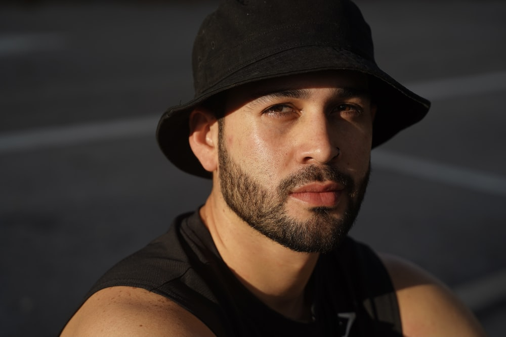 man in black tank top wearing black hat