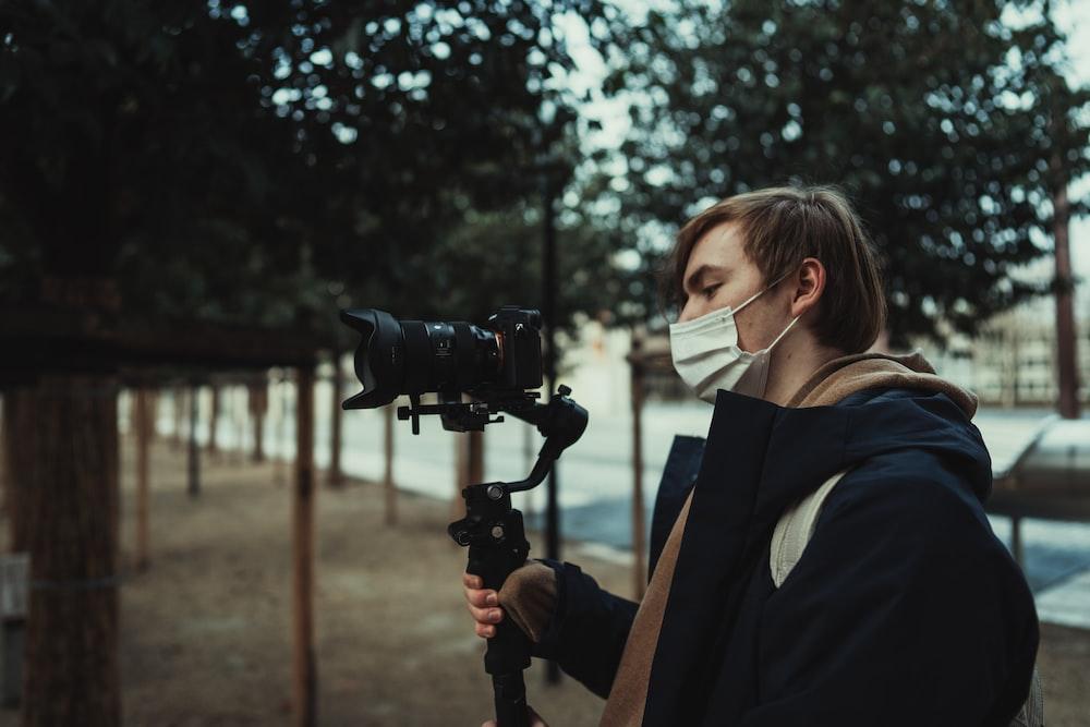woman in black blazer holding black dslr camera