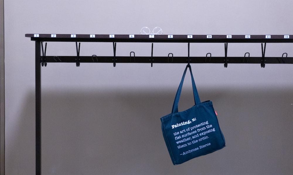 blue tote bag hanging on black metal bar
