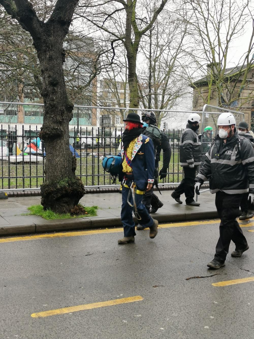 people in green jacket walking on pedestrian lane during daytime