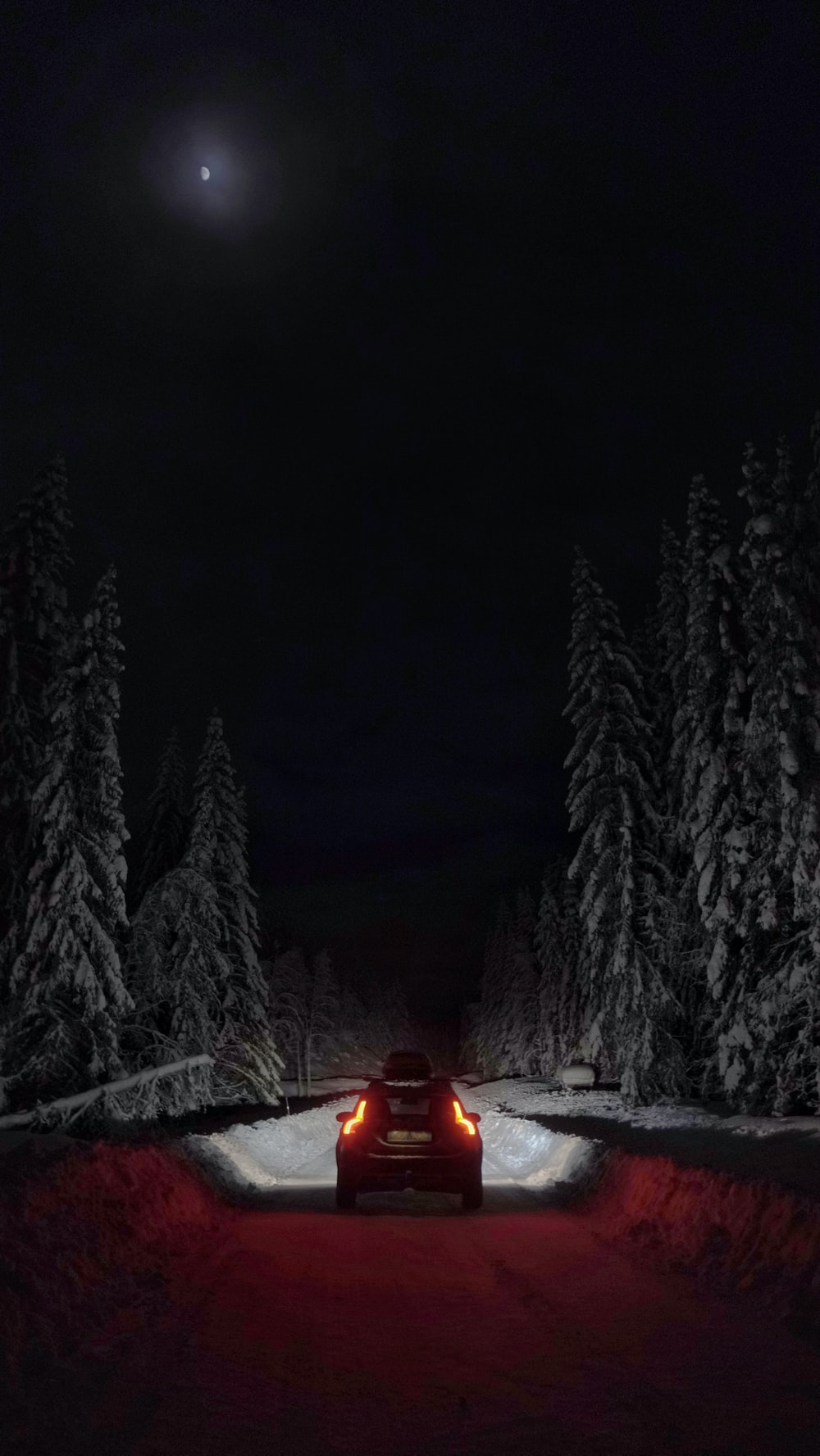 person in red jacket sitting on snow covered ground during night time