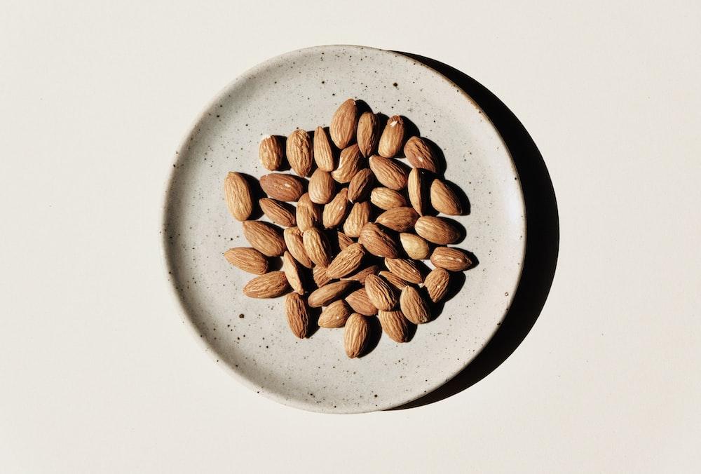 brown coffee beans on white ceramic bowl